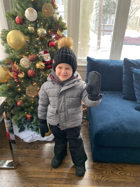 a boy in front of a christmas tree