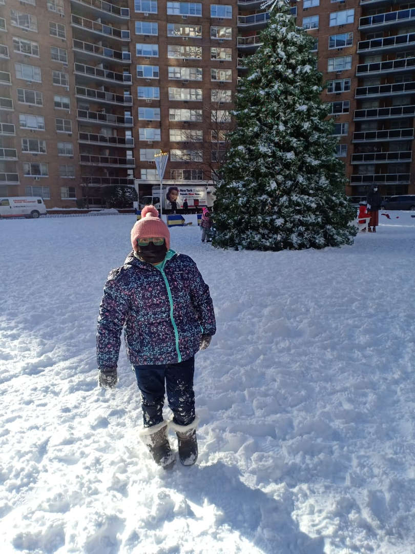 a boy in front of  a big christmas tree in the snow