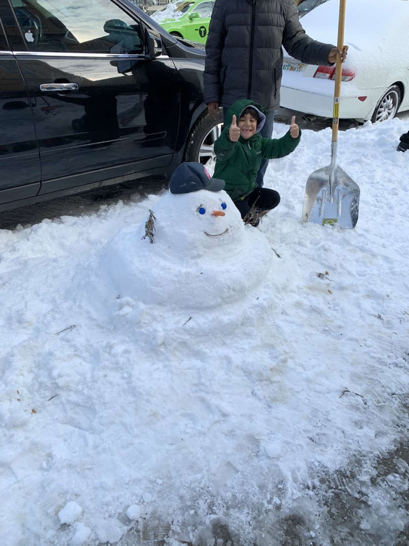 a kid with a snowman and a shovel