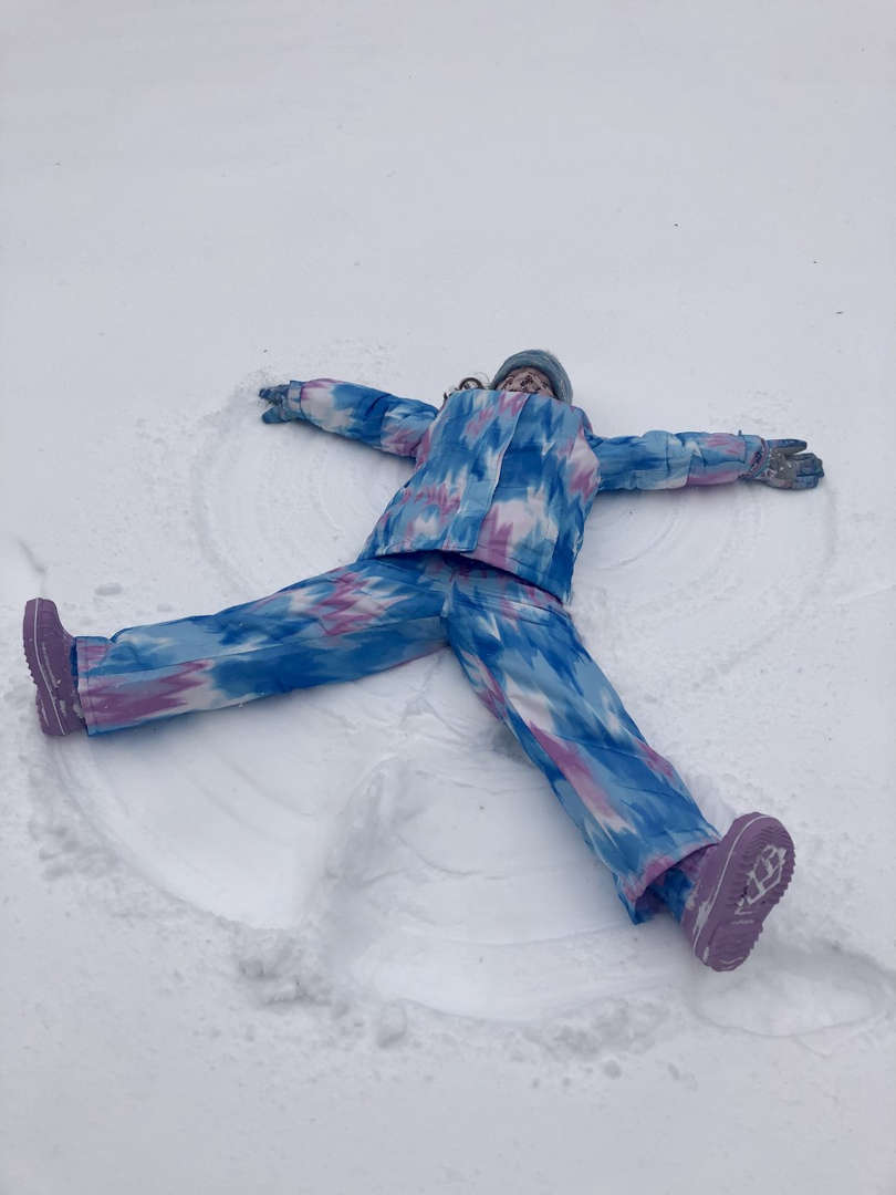 a kid in blue making a snow angel
