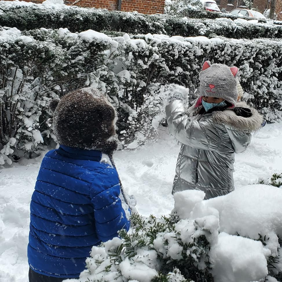 two children playing in the snow throwing snowballs