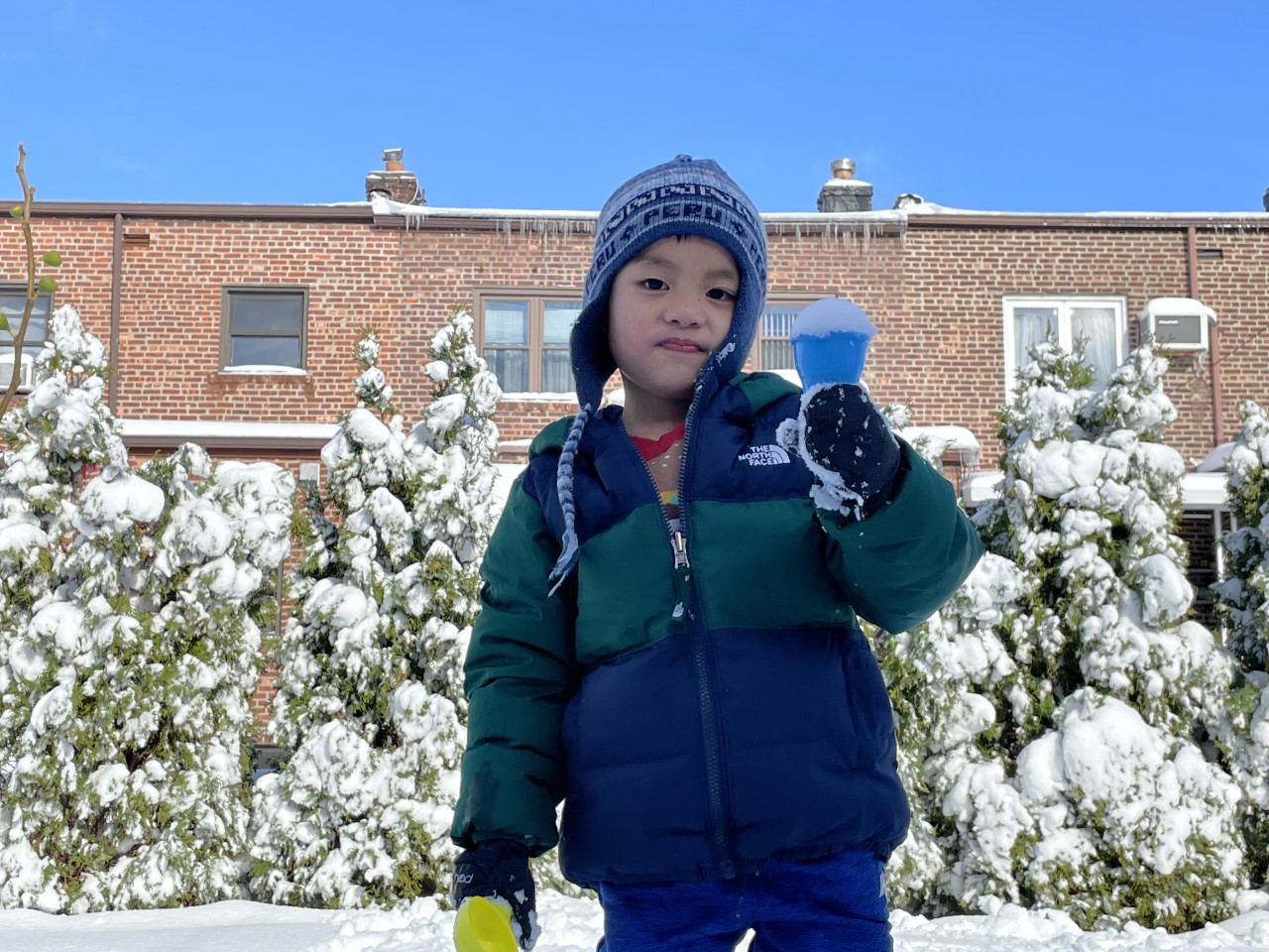 a boy in front of a building holding snow