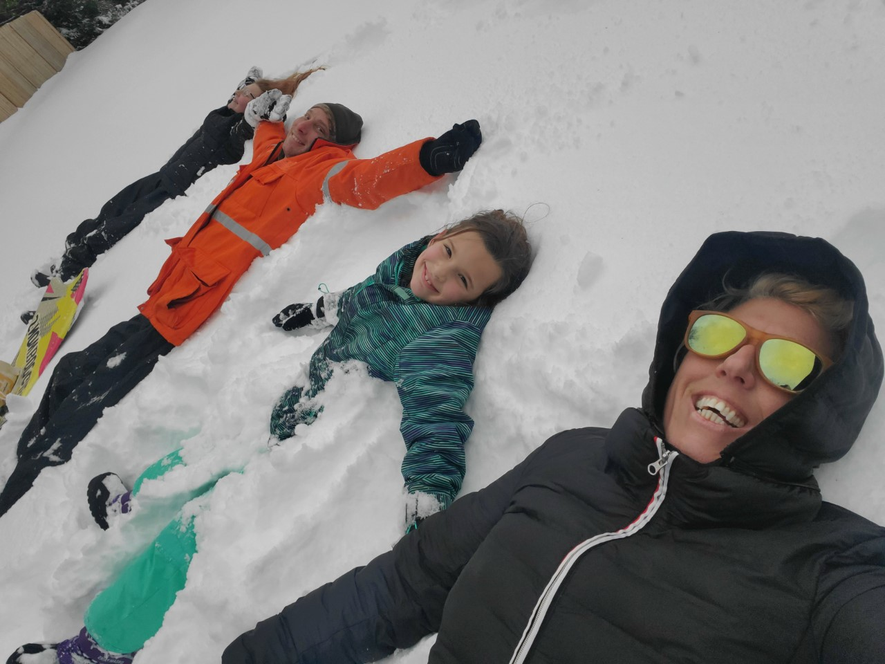 three kids and one adult on the ground in the snow