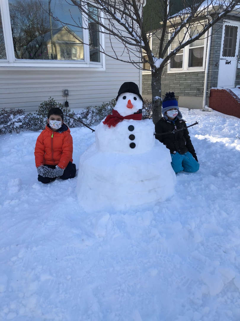 two kids with a big snowman