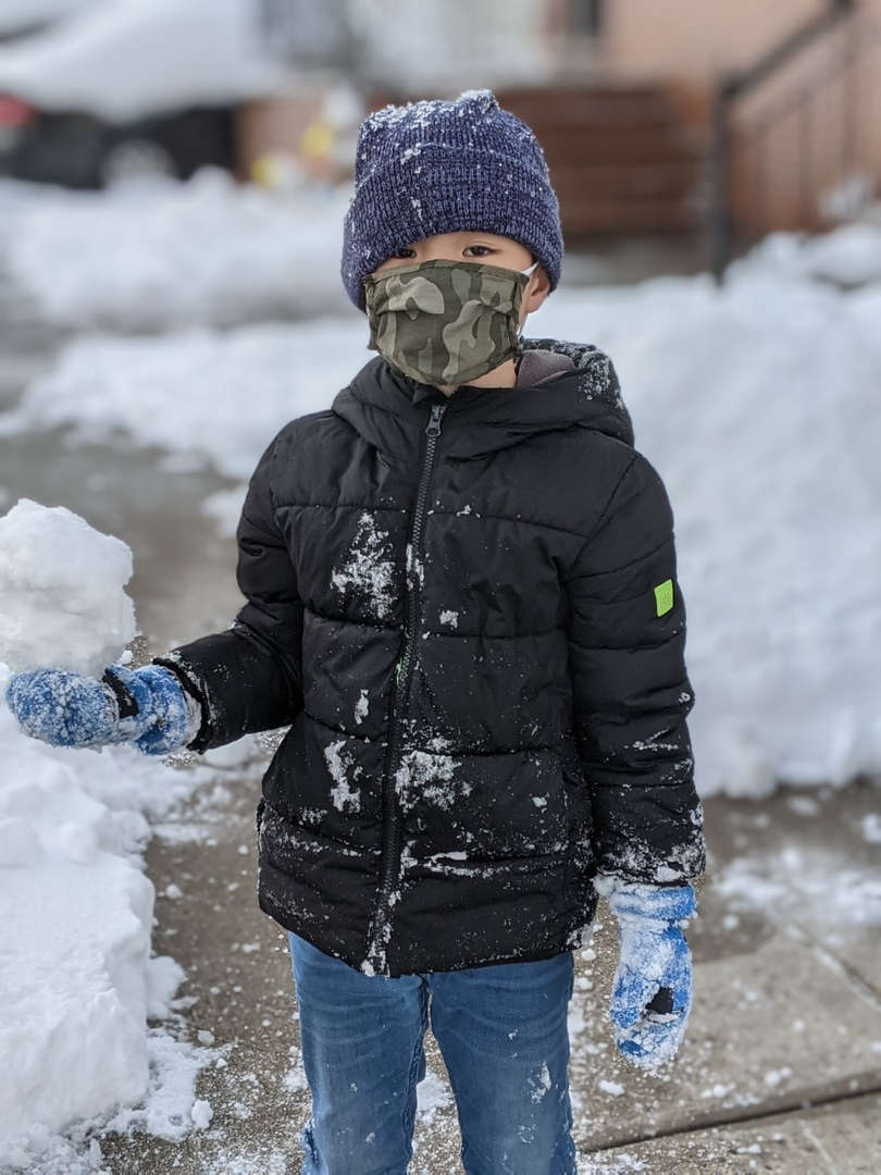 a boy in black jacket holding snow on his hand