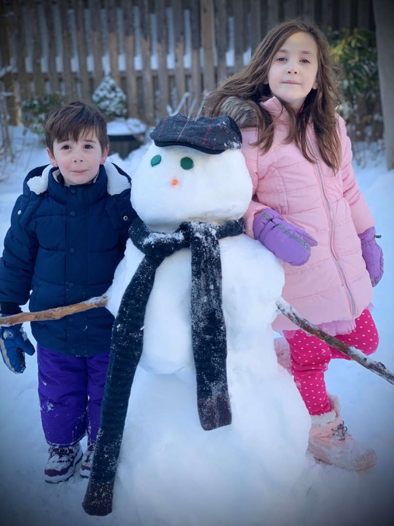 one boy and one girl with a snowman