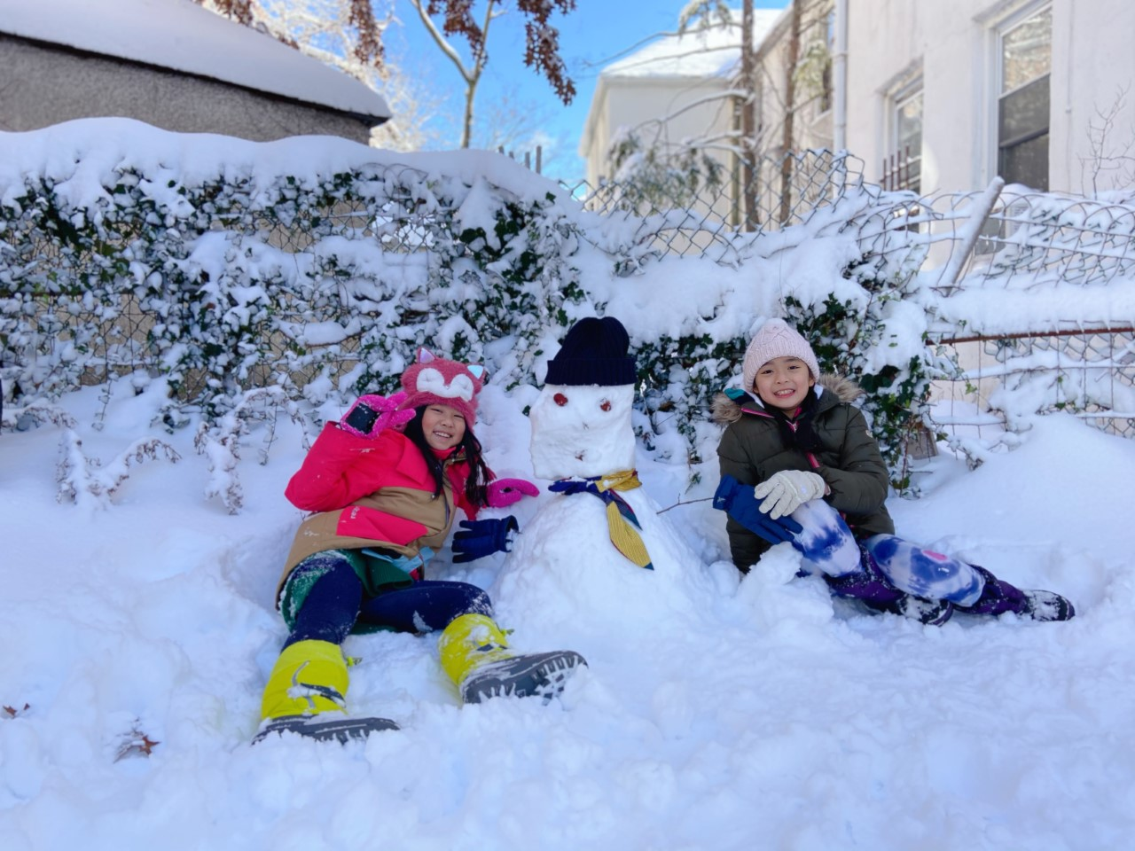 two kids on the ground with a big snowman