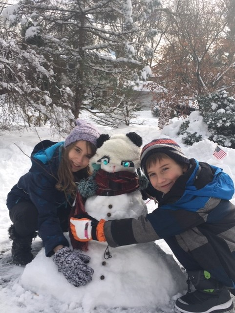 two kids with a snowman smiling