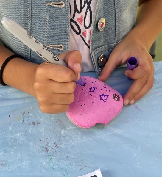 Painting a pink rock.