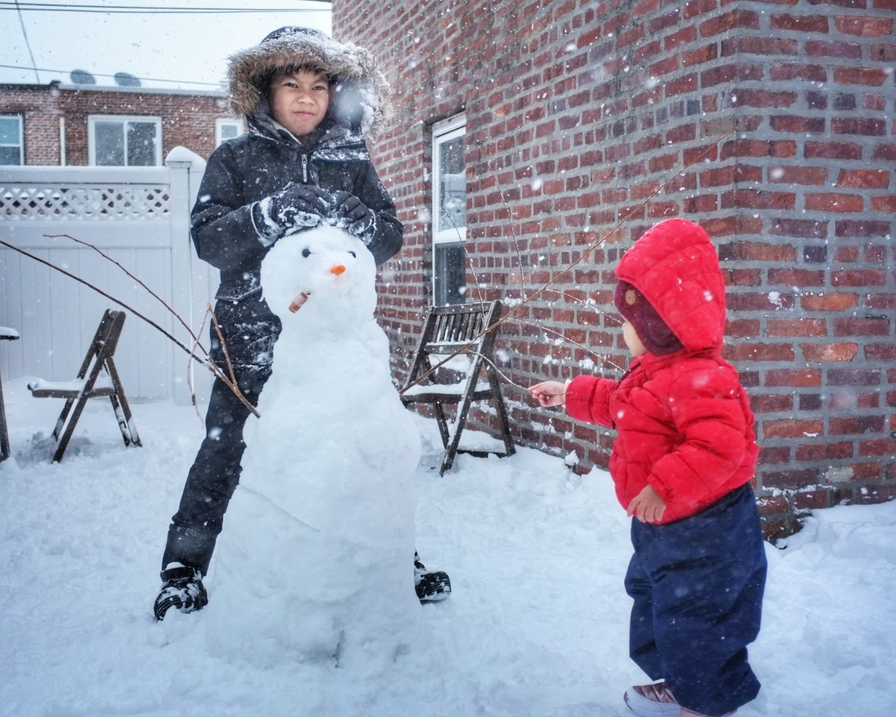 two kids building a snowman