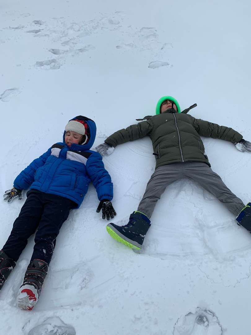 two children lying on the ground in the snow