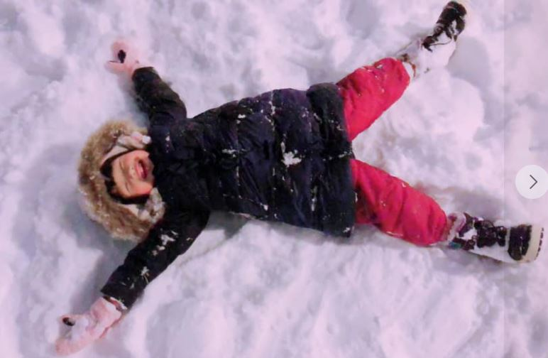 a kid in red pants making a snow angel