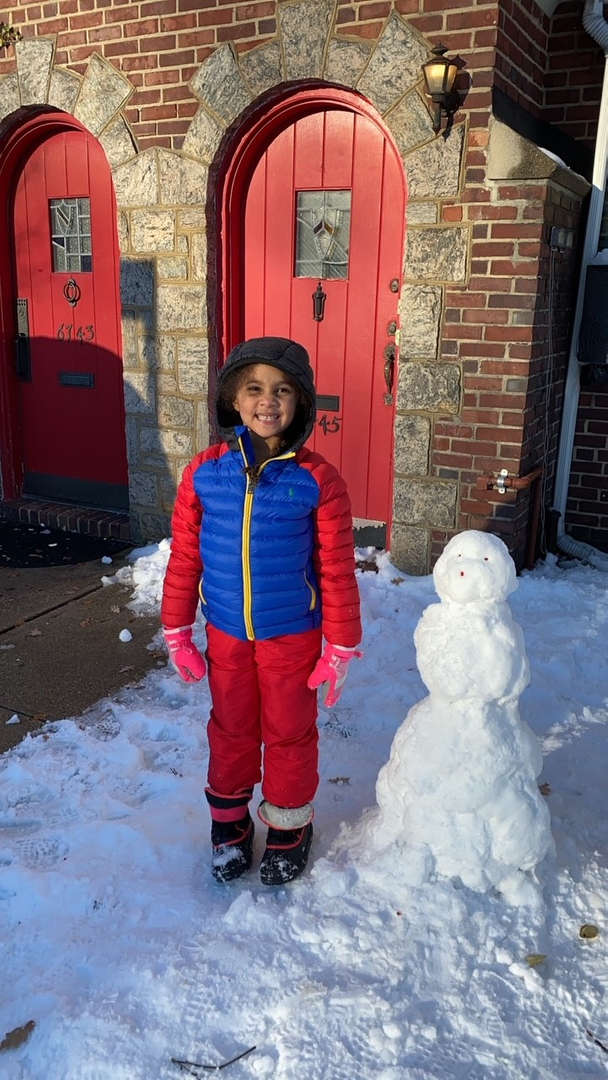 a girl in red suit standing next to a snowman