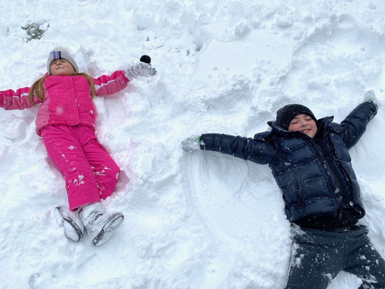 one girl in pink and a boy in black coat making a snow angel