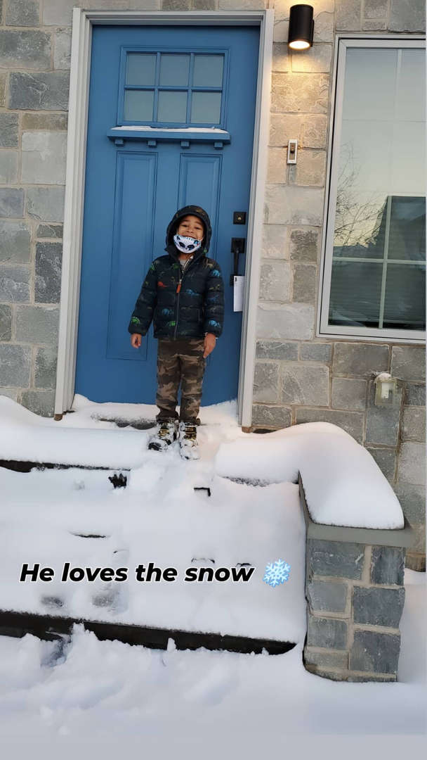 a boy in front of a house with a blue door in the snow