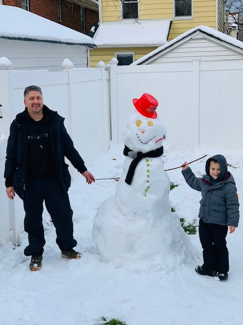 a man and a boy next to a big snowman with a red hat