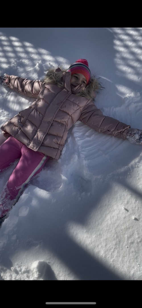 a girl  in pink pants making a snow angel on the ground