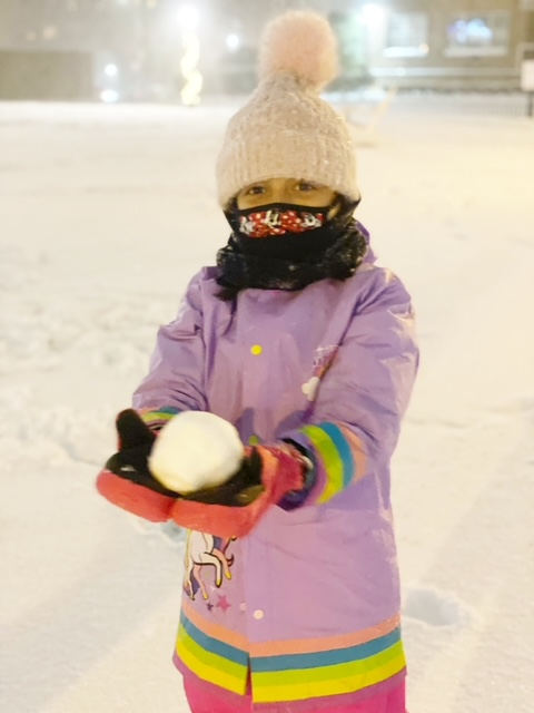 a girl in purple holding a snowball