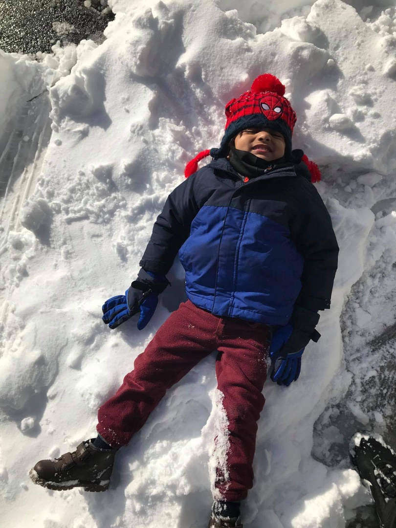 a boy on the ground in the snow