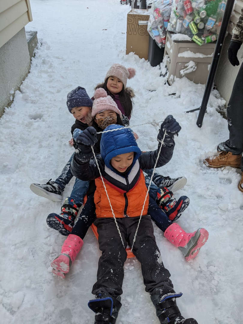 four kids on a sled coming down a hill