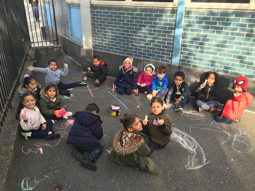 Students sitting on playground and chalk