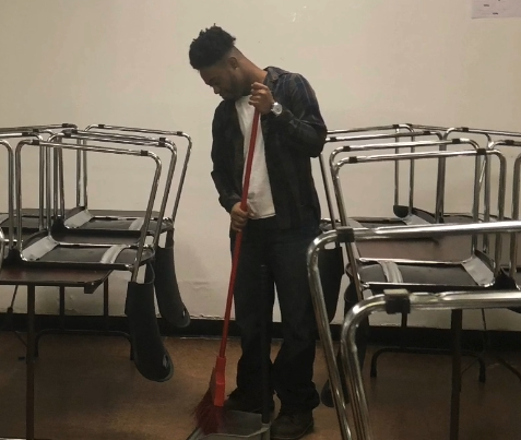 Student helping sweep at the Glebe center