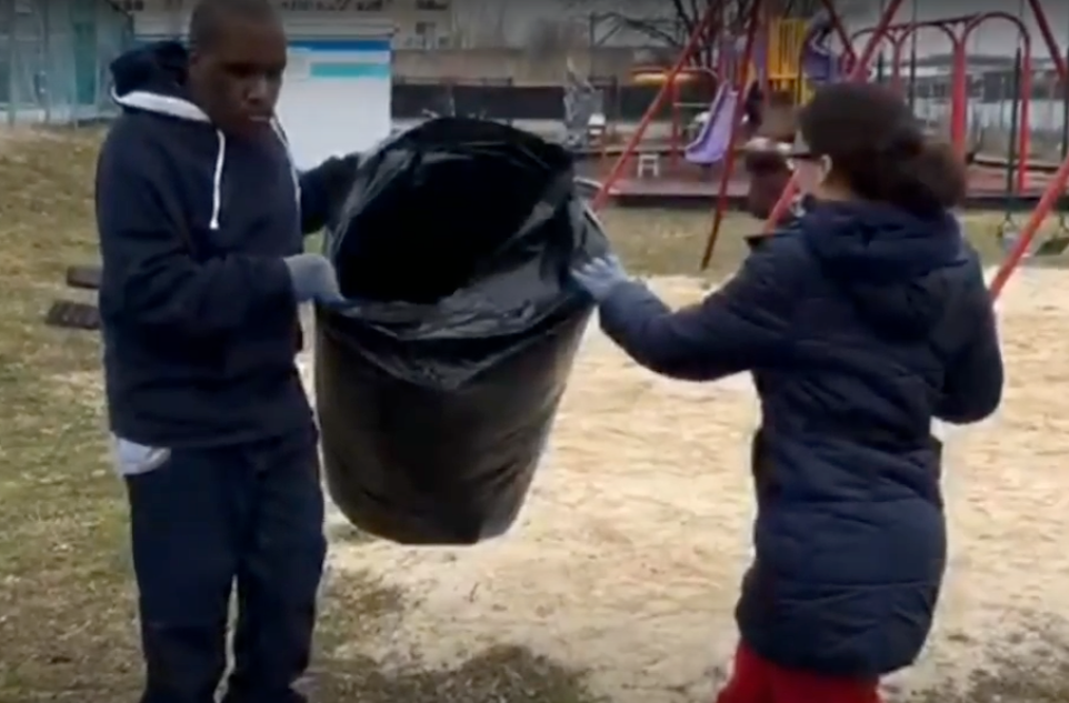 Students holding trash can YMCA