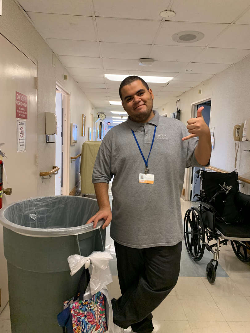 Student with trash can during Plaza program