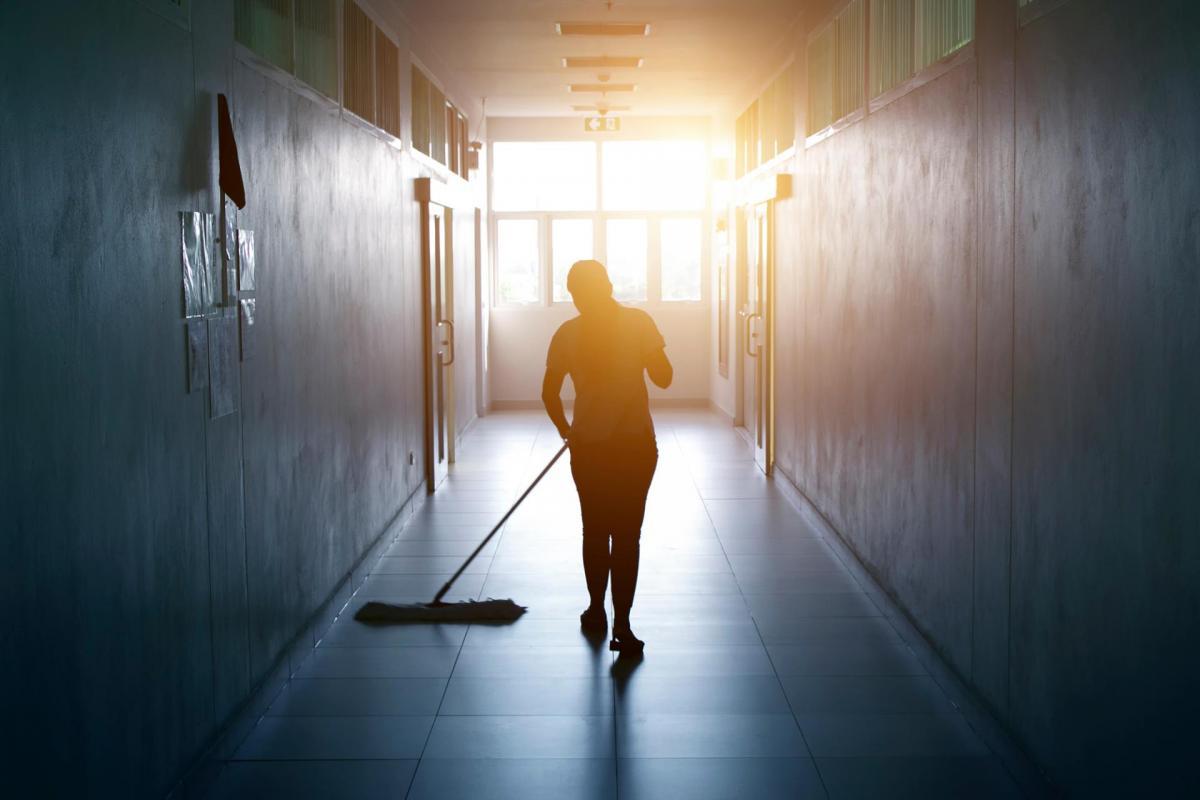 Custodian sweeping a hall in a school building