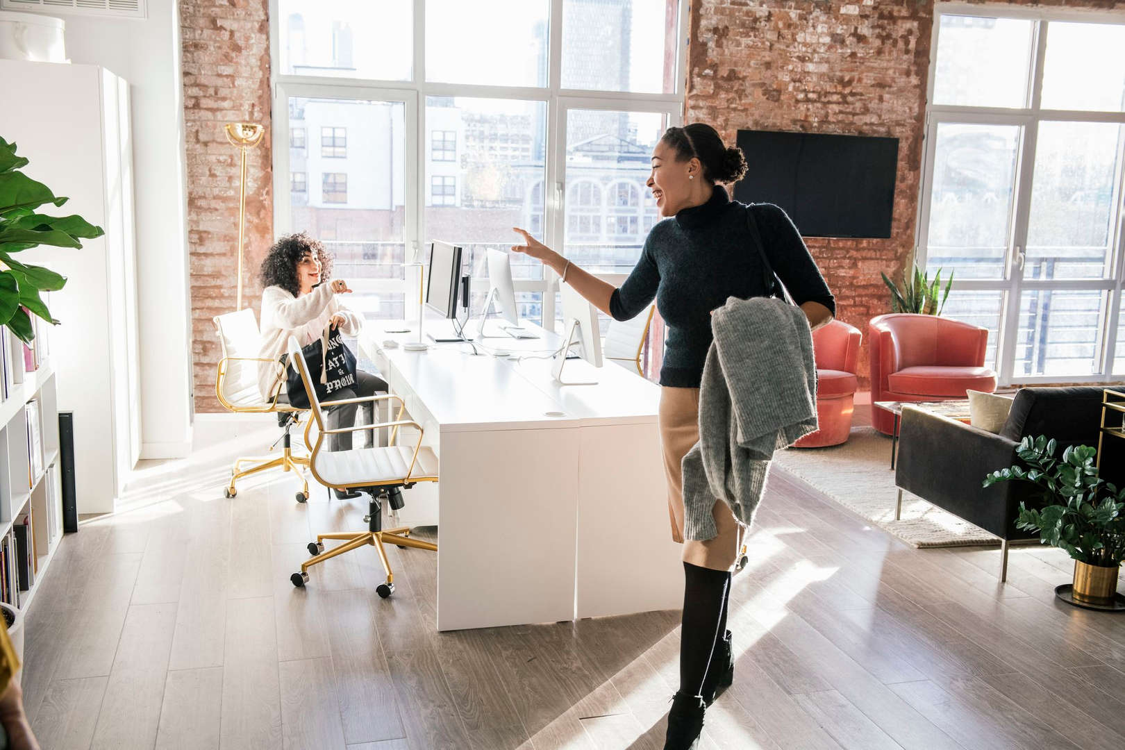 Woman leaving office waving to colleague