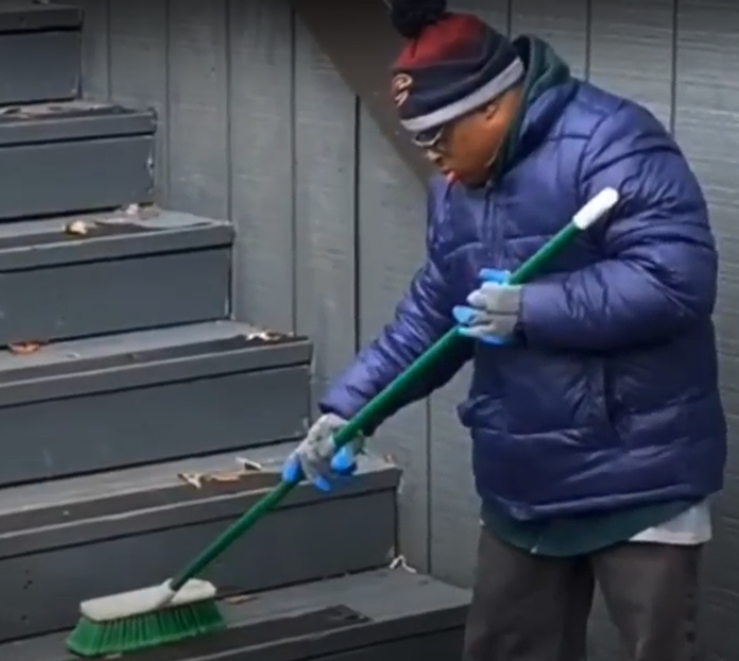 Student sweeping stairs YMCA program