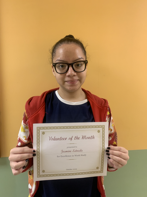 """Student holding a """"Volunteer of the Month"""" certificate"""