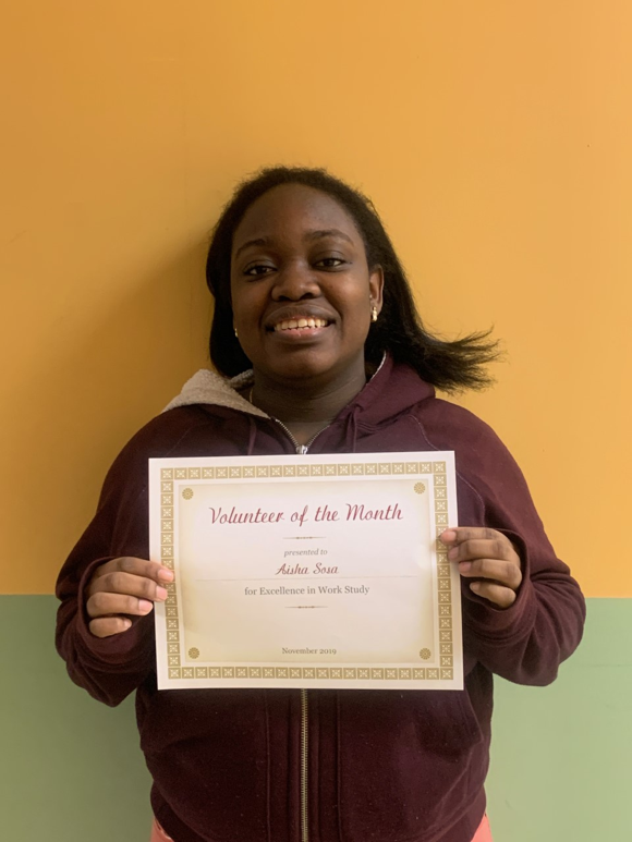 """Student with smile holding a """"Volunteer of the Month"""" certificate"""