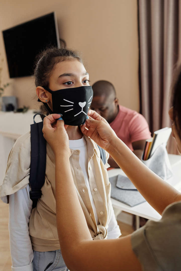 Student putting on mask before leaving home