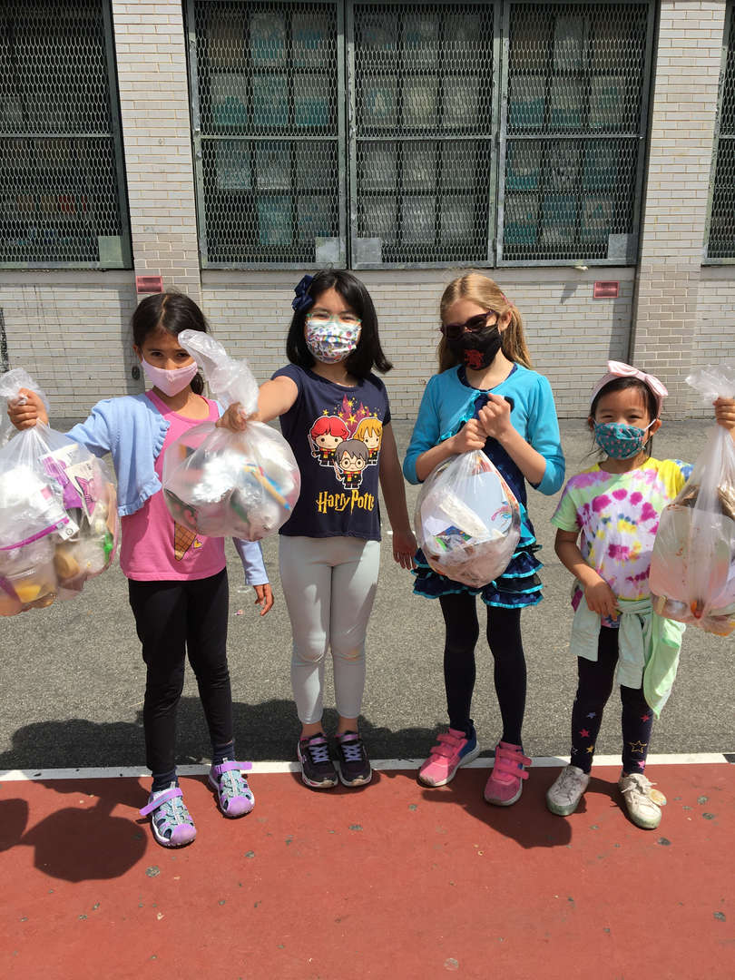 Students holding full trash bags.