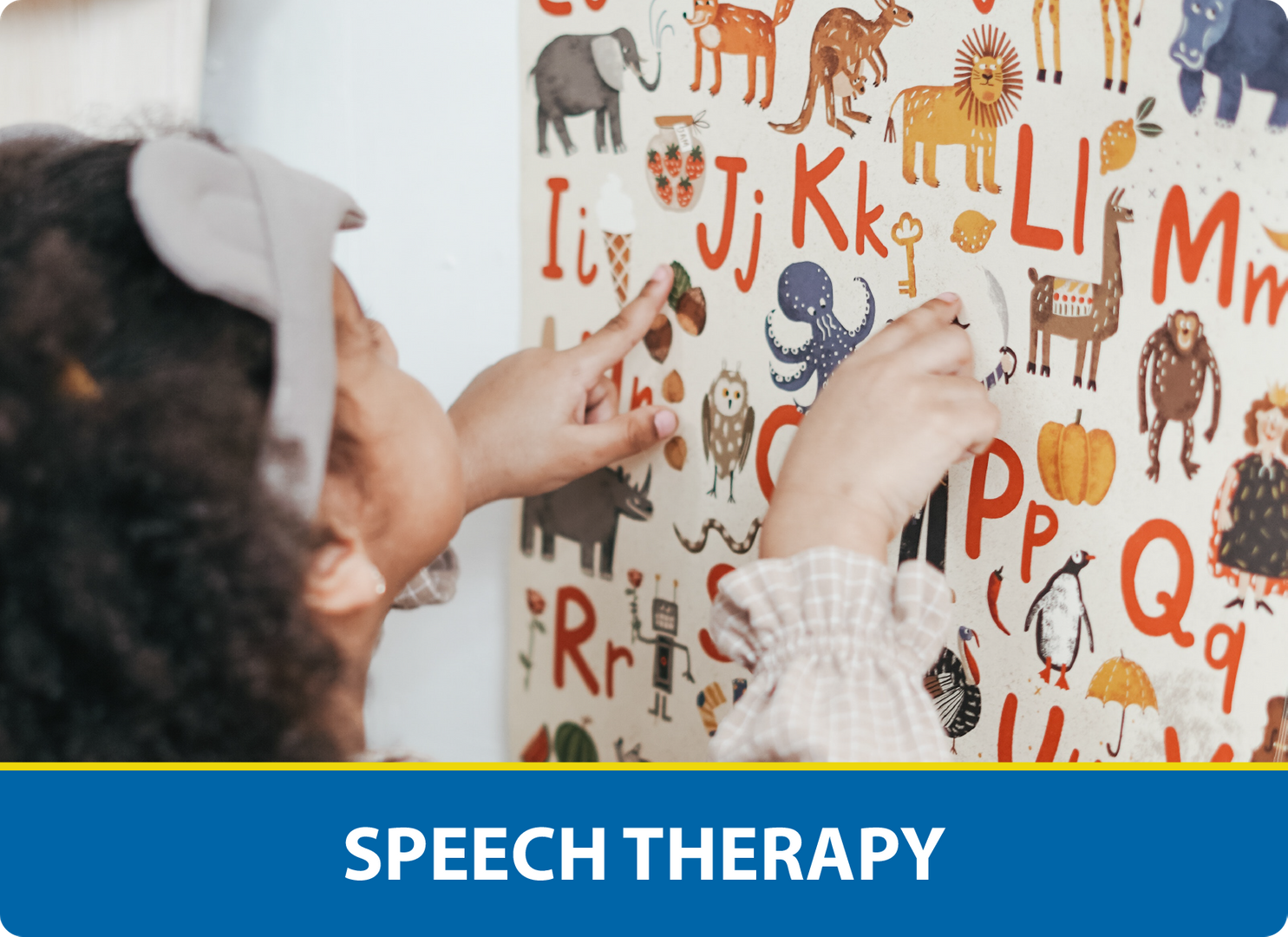 Speech Therapy: Girl pointing at alphabet poster