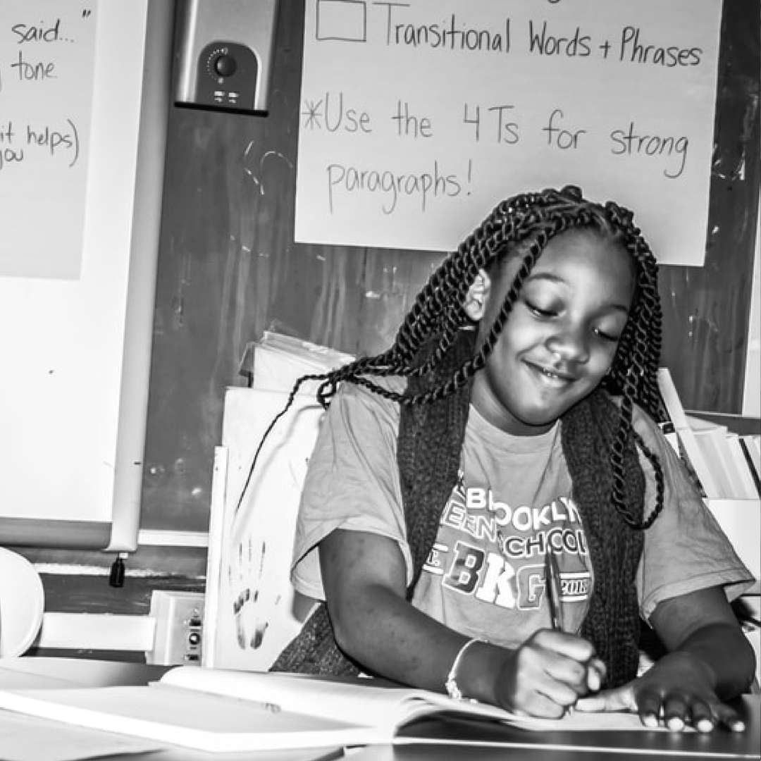 Student smiling and writing on her worksheet