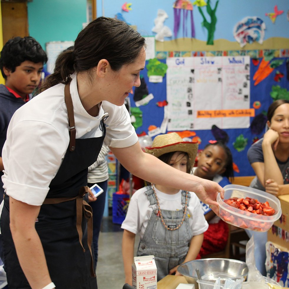Teacher in an apron handing a container of strawberries to student