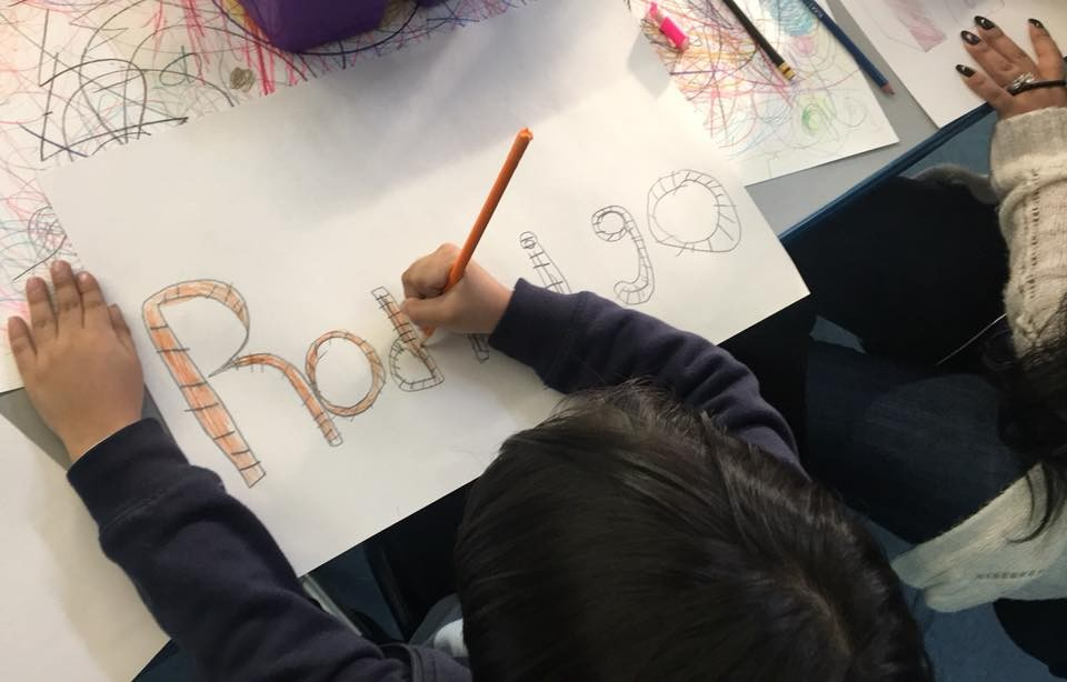 Student writing his name, Rodrigo, in colored pencil