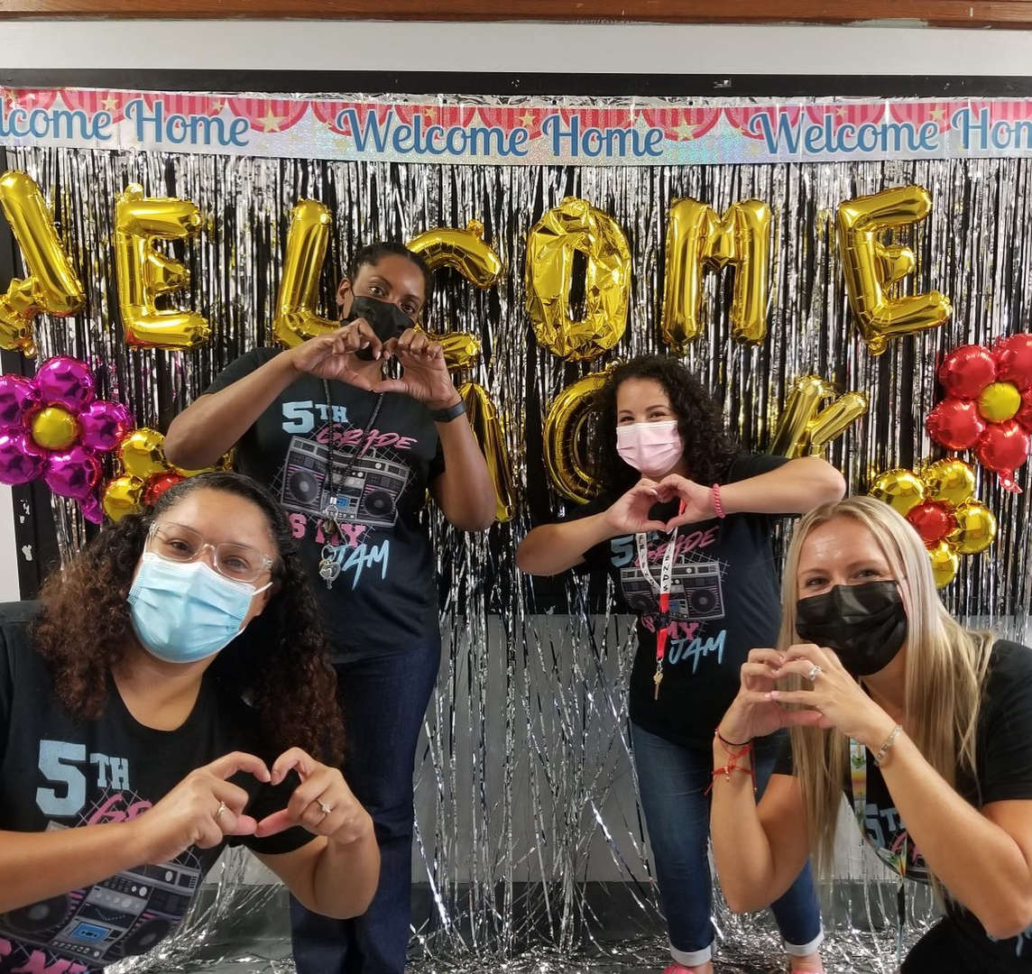 Teachers standing in front of a welcome back bulletin board making heart signs with their hands.
