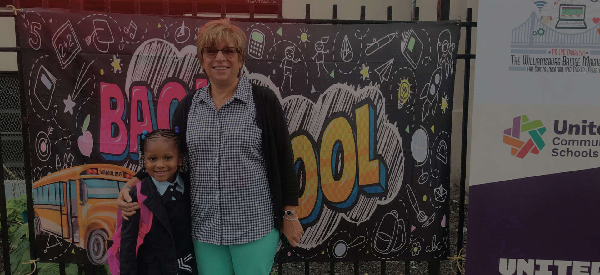 Principal Colon and a student in front of a Back to School banner