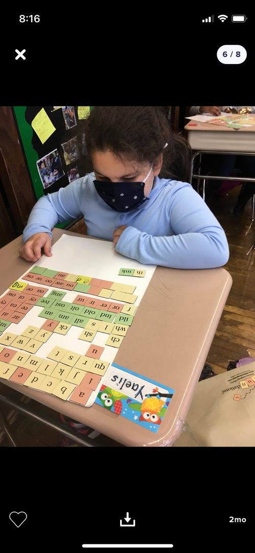 Students with a magnet board and letter tiles.