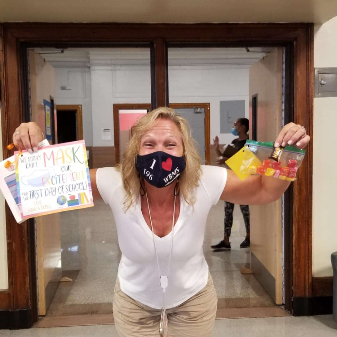 Teacher holds up mask and sign that says we can't mask our excitement for the first day of school.