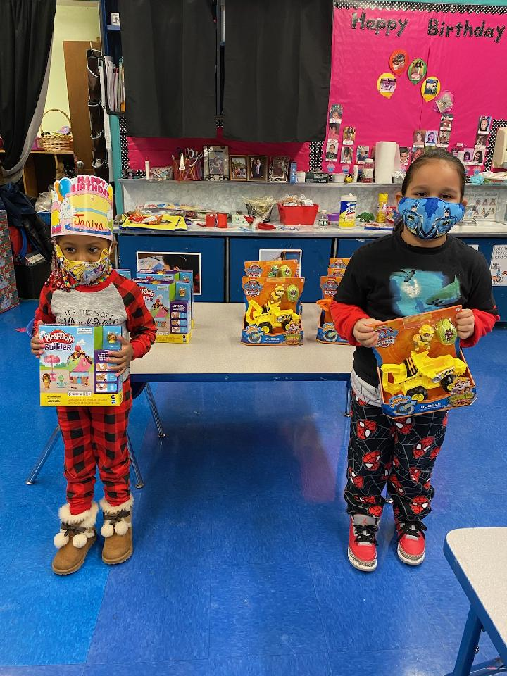 Two young children in pajamas hold up a toy for the holidays.