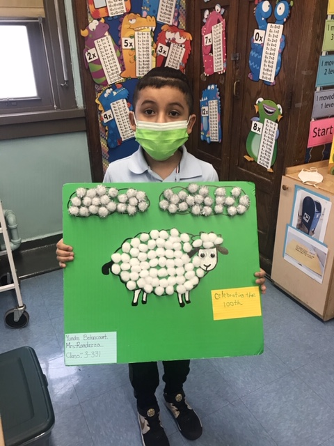 A student holds up a poster board with a sheep made of cotton balls.