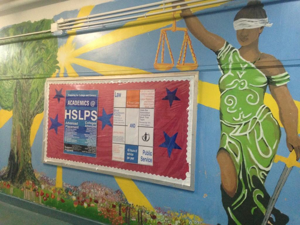 Bulletin board on a wall painted with a mural of Lady Justice