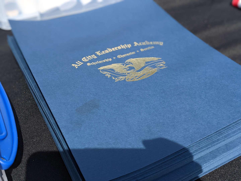 Graduation certificates in folders.