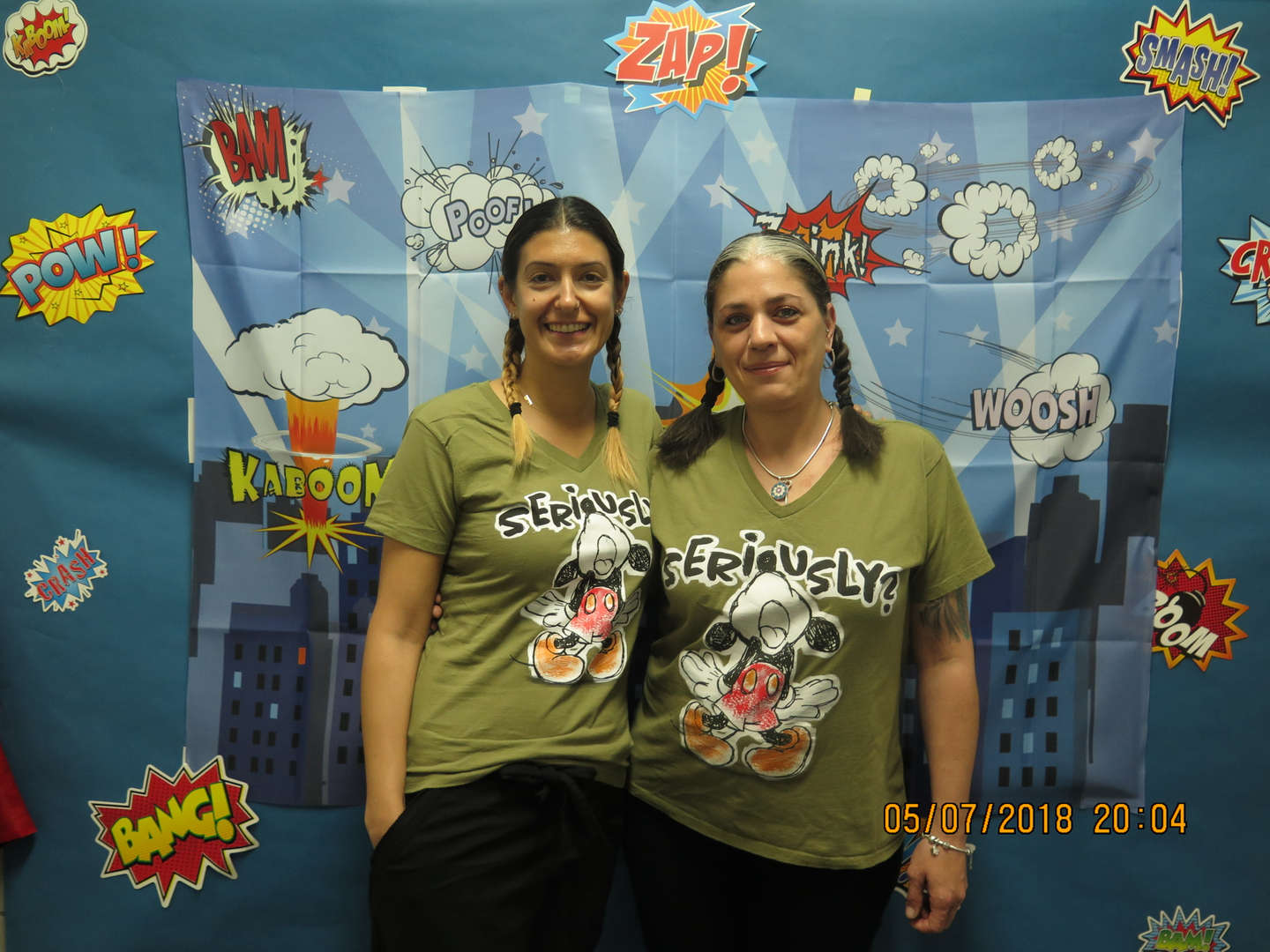 Teachers in Mickey Mouse shirts in front of a comic themed backdrop