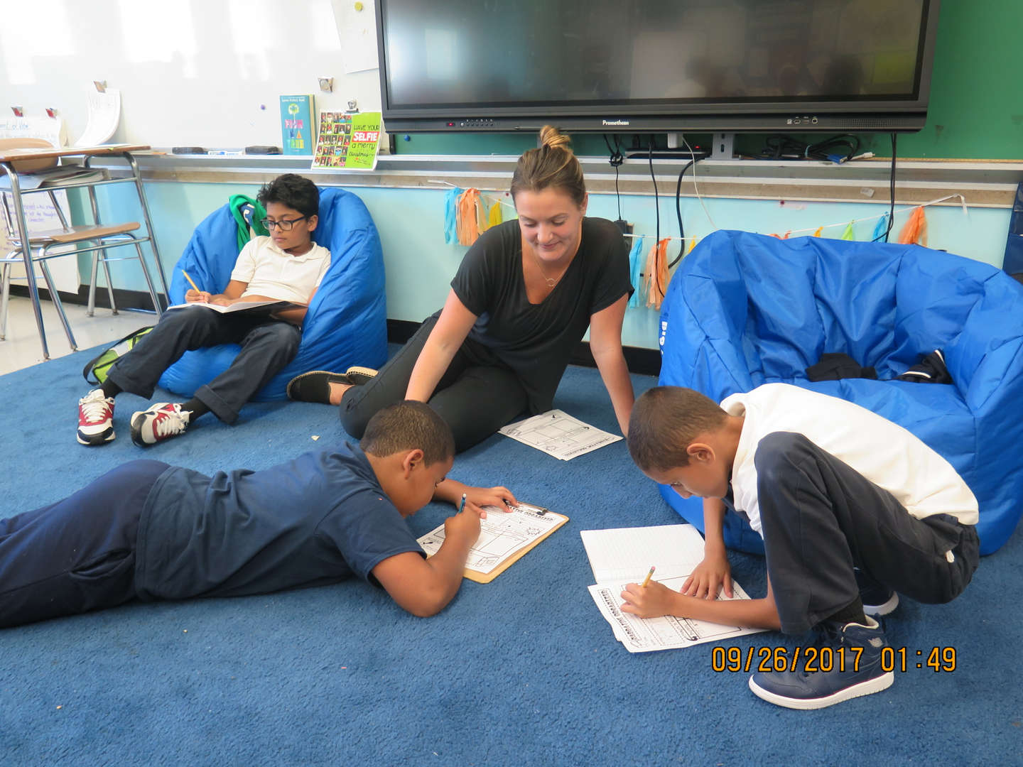 Teacher working with students on the class rug