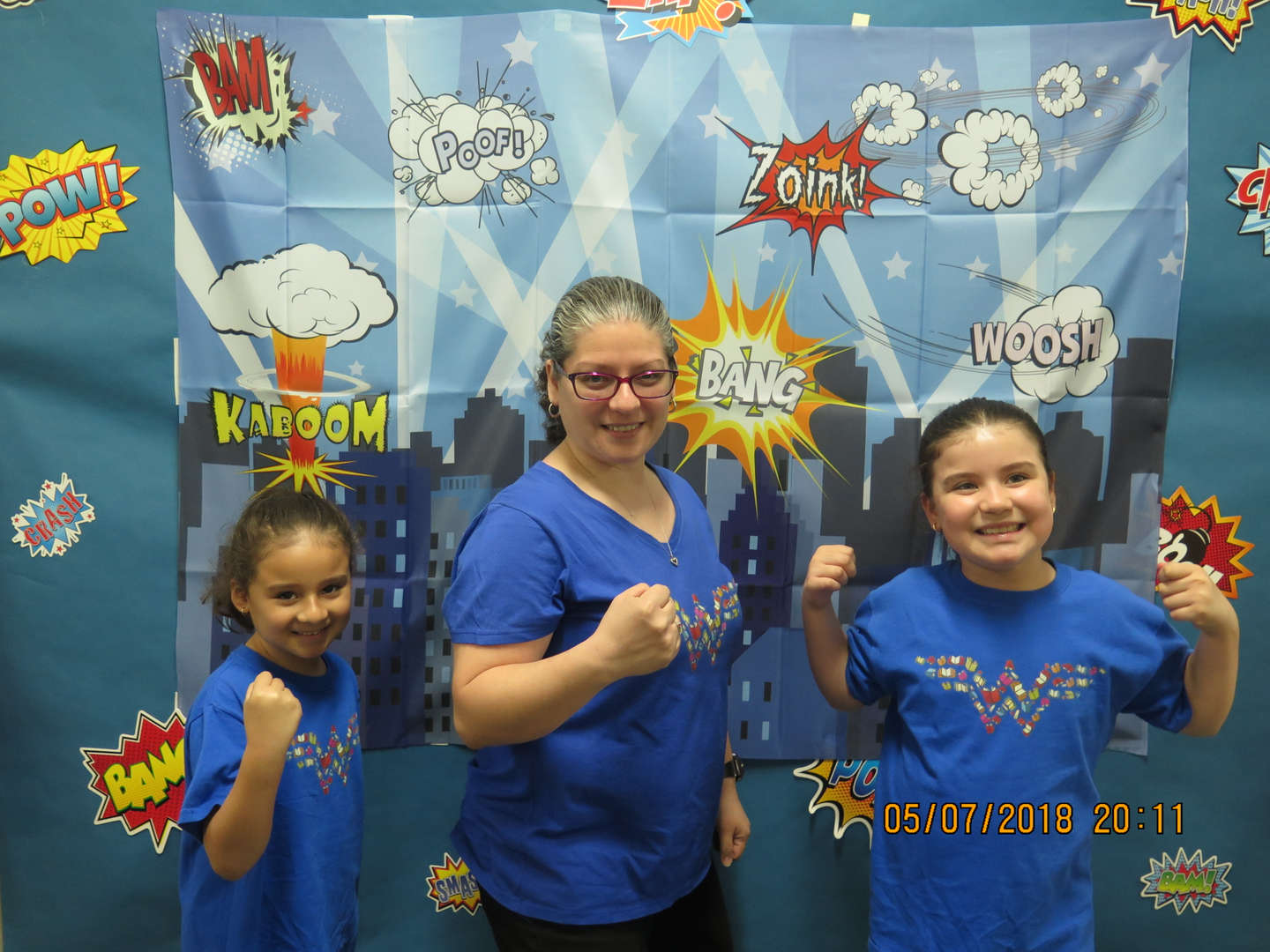 Teacher and students in Wonder Woman shirts in front of a comic themed backdrop